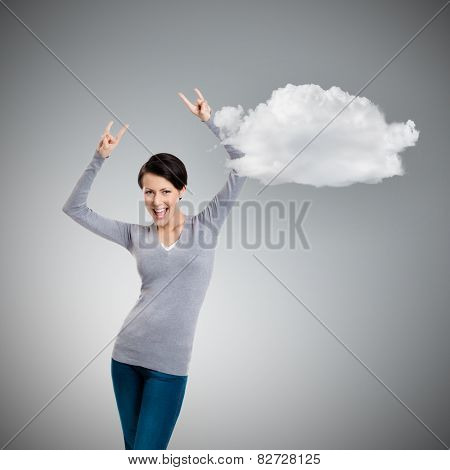 Glad pretty woman puts her hands up with two fingers pointed up, isolated on grey background with cloud