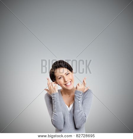 Young woman shows crossed fingers, isolated on grey