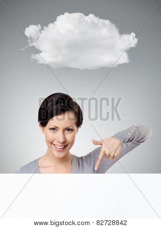 Young woman points down with forefinger , isolated on grey background