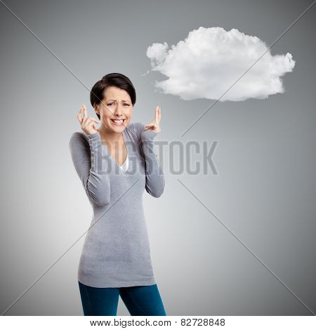 Hoping young woman shows crossed fingers, isolated on grey background with cloud