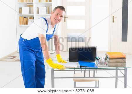 Smiling man cleaner wiping table at the office