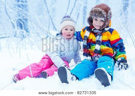Portrait Of Little Girl And Boy In Winter Hat In Snow Forest At Snowflakes Background
