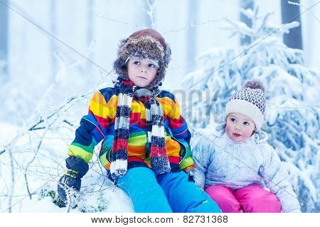 Portrait Of Two Kids: Boy And Girl In Winter Hat In Snow Forest