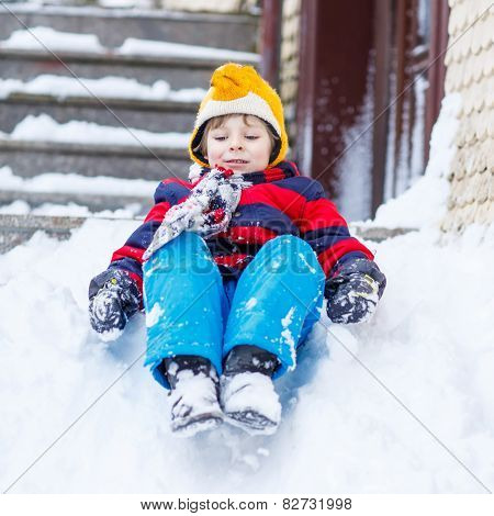 Happy Child In Colorful Clothes Having Fun With Riding On Snow, Outdoors