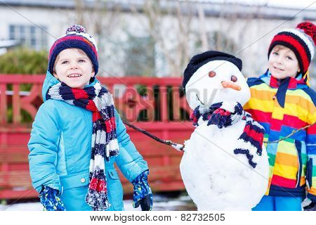 Two Little Siblings Boys Making A Snowman, Playing And Having Fun With Snow