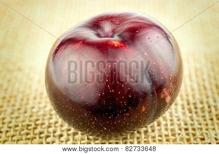 Rustic Shot Of Whole Plum Against Burlap Hessian Background