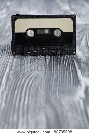 Music Concept. Black Audio Cassette On The Gray Wooden Background. Vintage, Retro Style. Soft Focus.