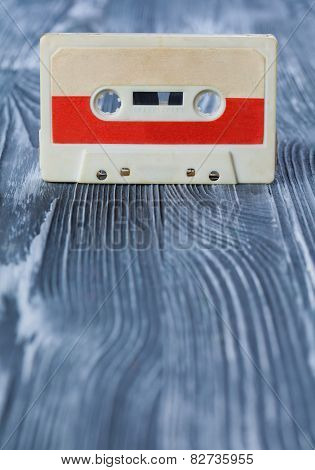 Music Concept. Bright Red Audio Cassette On The Gray Wooden Background. Vintage, Retro Style. Soft F