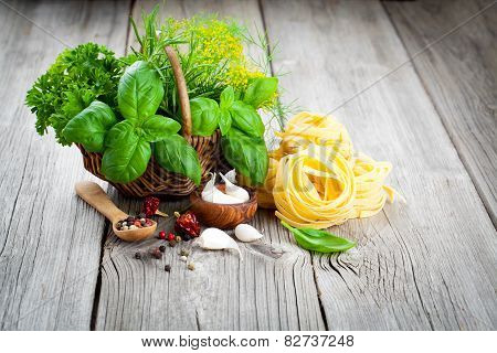 Italian Pasta Fettuccine Nest With Wicker Basket Of Green Herbs On Wooden Background