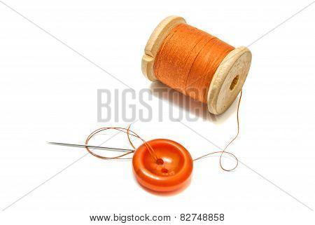 Orange Spool Of Thread, And Button On White