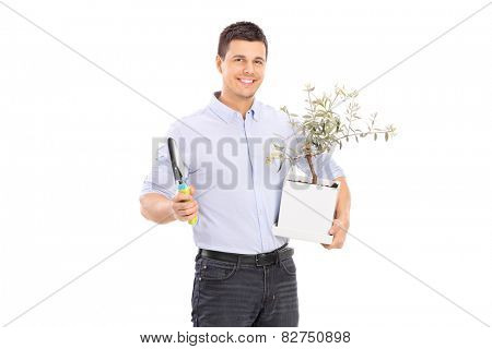 Young man holding an olive tree plant and a spade isolated on white background