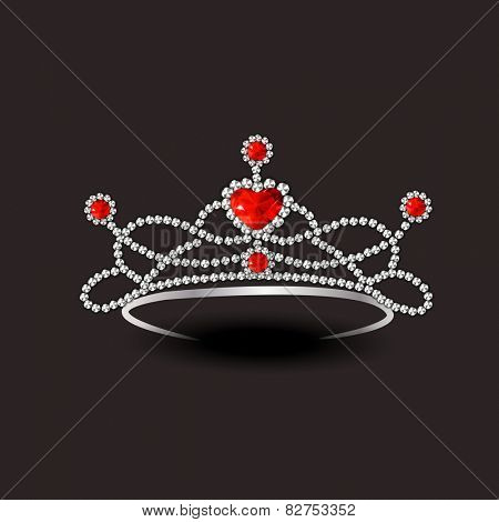 Beautiful stylish diamond tiara with red rubies on dark brown background.