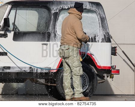 Man Washing His Car With A Jet Of Water