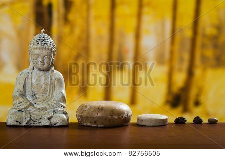 buddha sculpture with soaps and stones spa concept