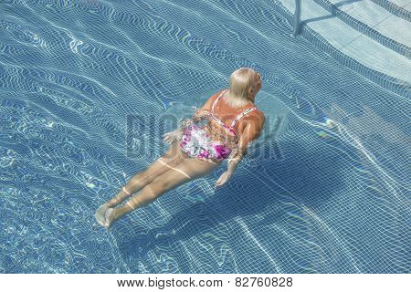 Aged Woman Is Emerging From The Blue Water Of Pool.