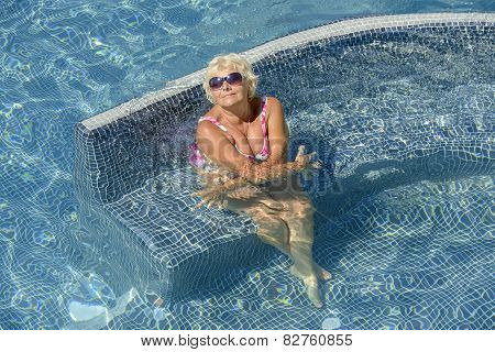 Aged Woman Is Sitting In Water Of Pool.