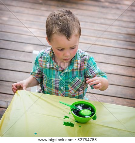 Boy Watches His Easter Egg In The Green Dye