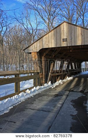 Walkway leading to a covered bridge on a snowy day