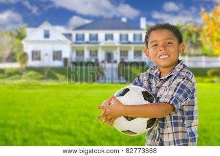 Cute Mixed Race Boy Holding Soccer Ball In Front of Beautiful House.