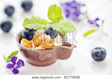 Blueberry And Mascarpone Dessert In Chocolate Cup, Garnish With Caramelized Walnuts And Mint