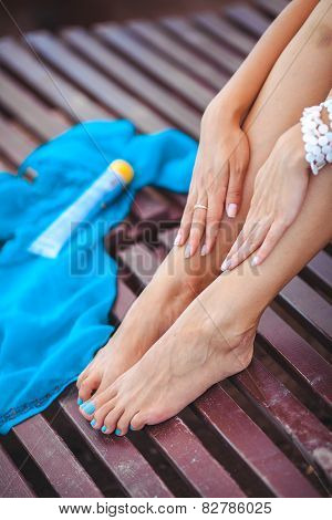 Beautiful legs of a young woman sunbathing on a lounger.