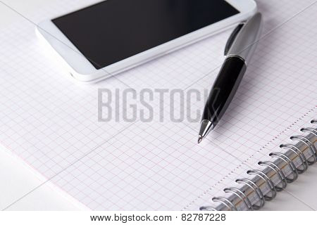 Note Book With Checked Pages, Pen And Smart Phone
