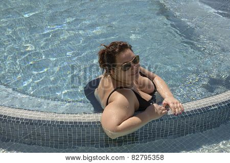 Mid Adult Woman Is Sitting In Water Of Pool.