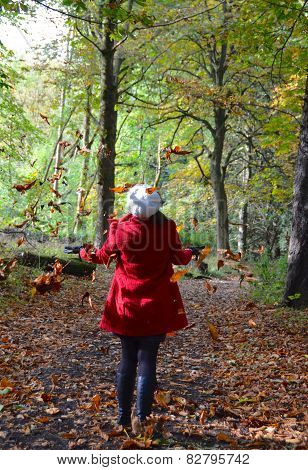 Girl with falling leaves in autumnal woods