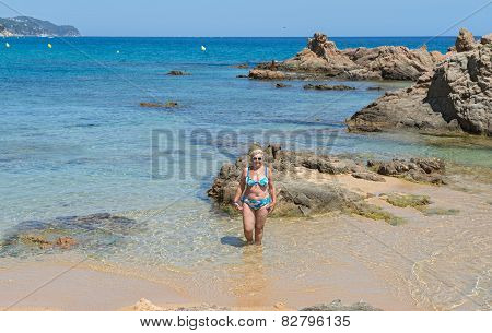 Aged Woman Is Standing On The Beach Sand Between Rocks.