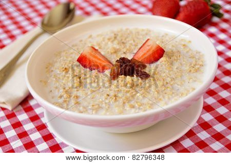 closeup of a bowl with porridge with sultana raisins and strawberry, on a set table for breakfast