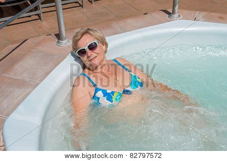 Happy Aged Lady Is Lying In Jacuzzi In The Sun.