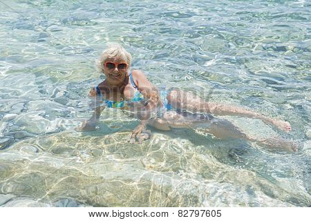 Woman Lie In Clear Transparent Sea Water.