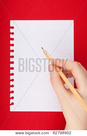 Torn blank lined notebook page with hand holding pencil on red