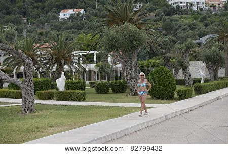 Woman In Swimsuit At The Park Of Sveti Stefan, Montenegro.