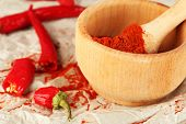 stock photo of pepper  - Ground red pepper in mortar with chili pepper on table close up - JPG