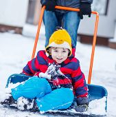 picture of snow shovel  - Funny kid boy having fun with riding on snow shovel during his father cleaning road from snow outdoors on cold day - JPG