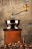 image of wooden box from coffee mill  - Wooden coffee grinder with roasted coffee beans on a wooden background - JPG