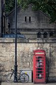 stock photo of phone-booth  - Red phone booth an iconic symbol of British heritage and an old bicycle on the streets of oxford England - JPG