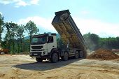 pic of truck-cabin  - big tipper truck unloading land on the site - JPG