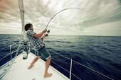 image of rig  - Young man fishing in open sea from sail boat - JPG