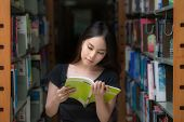 picture of mixed race  - A portrait of a mixed race college asia student at campus in library and read a book - JPG