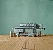 image of calculator  - vintage calculator and gold coins against the background of the old wall and wood table - JPG