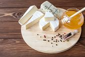 stock photo of brie cheese  - cheese plate with Brie Camembert Roquefort and honey - JPG