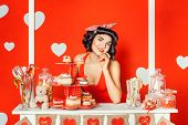 stock photo of sweet dreams  - PinUp Porter girl standing in a booth with cakes and sweets she leaned on the arm and dreams - JPG