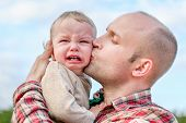 image of pity  - caring father calms toddler son outdoors on the sky background - JPG