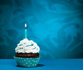 stock photo of icing  - Chocolate Cupcake with icing and lit birthday candle over a blue background - JPG