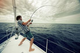 stock photo of sailing vessels  - Young man fishing in open sea from sail boat - JPG