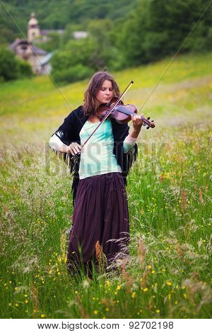 violinist on a meadow full of flowers, Young girl playing music instrument
