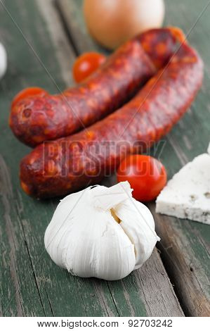 Whole Garlic Head In Front Of Two Sausages