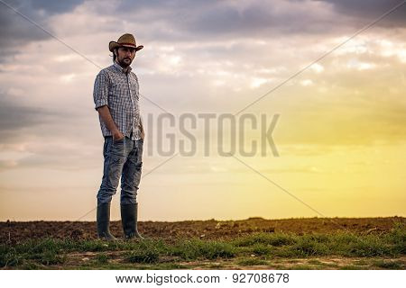 Male Farmer Standing On Fertile Agricultural Farm Land Soil